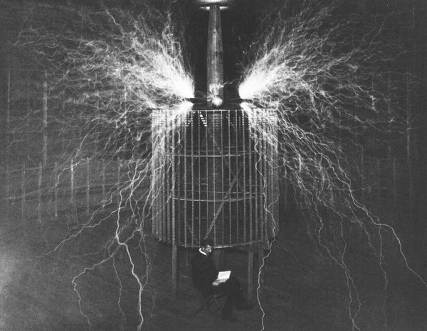 Largest Sparks Ever Produced by Man. Mr. Tesla is Seen Sitting. Seventy Feet Across Spark Streamers.