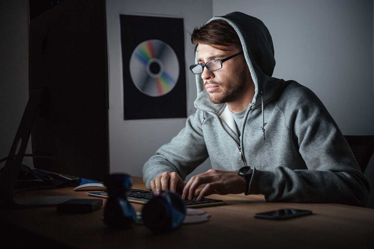 Thoughtful man in glasses and hoodie working on computer to make money online