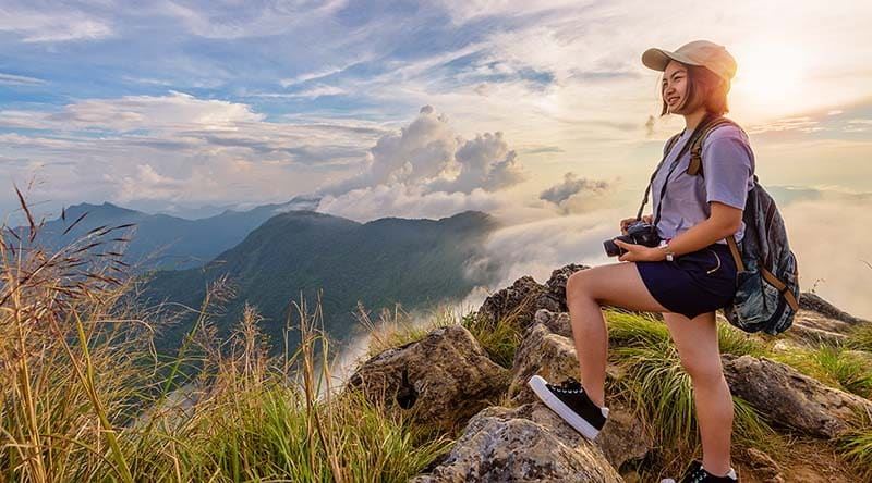 Girl tourist on mountains at sunset